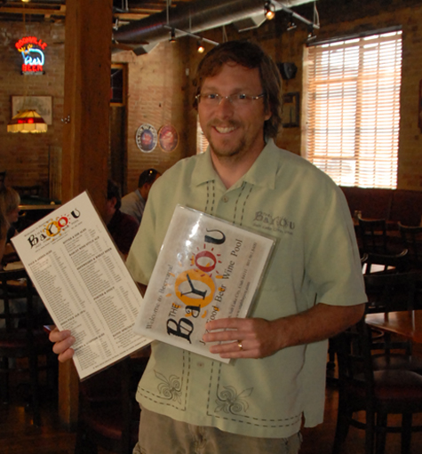 Owner MarkAlston proudly displays the Bayou's mammoth beer menu.