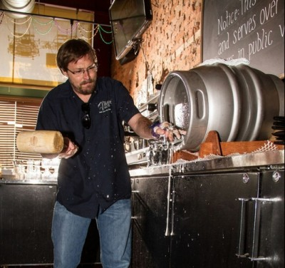 The Bayou owner Mark Alston drives a spout into a firkin cask with a wooden hammer for an entirely gravity-poured, charmingly tepid beer.