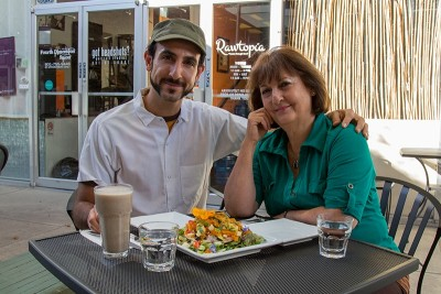 (L–R) Omar Abou-Ismail and Jinan Abu-Ismail sit before Rawtopia's Hemp Milk Chai and Hummus Pizza, whose crust and seed cheese Jinan added to Omar's raw-food cuisine.