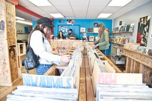 (Center) Alana Boscan and Adam Tye run Diabolical Records as customers Kamryn Feigel (L) and Brinley Froelich (R) peruse the vinyl selection.
