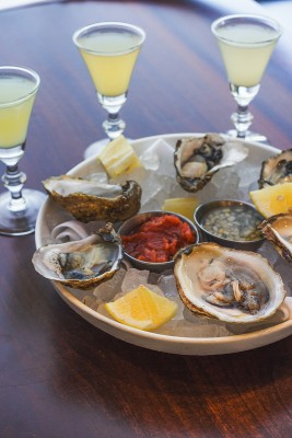 Raw oysters with Oyster Back cocktails showcase Current's seafood expertise.