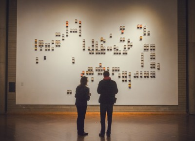 The cryptic message written on the wall awaits deciphering as a couple gazes in wonder. Photo: Talyn Sherer