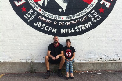 (L–R) Josh and Heidi Belka sit in front of their mural homage to musician and labor rights activist Joe Hill.