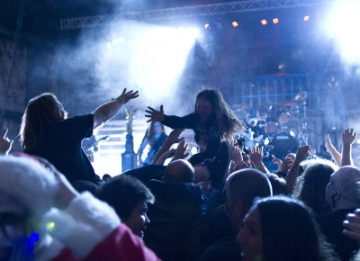 Two crowd surfers reach for each other's hands during King Diamond's set. Photo by Madi Smith.