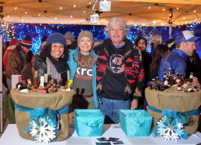 (L-R) KRCL board chair Daela Taeoalii-Higgs, Ellen Parrish, and KRCL DJ John Florence prepare an opportunity drawing for gift baskets of wine or high-point beer. Photo: John Barkiple
