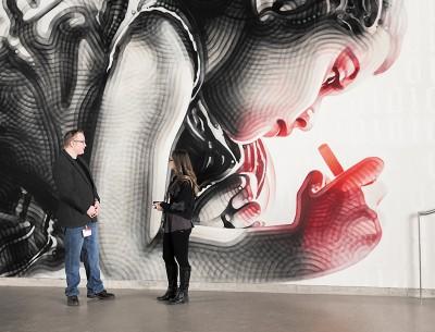 (L–R) Curator Andrew Ehninger and SLUG Senior Staff Writer Mariah M. Mellus stand before a mural by artist El Mac in Adobe's building in Lehi, Utah.
