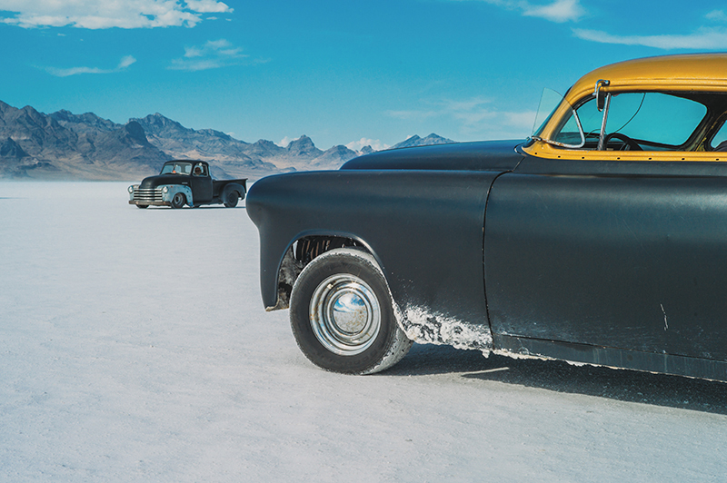 A 1953 Pontiac Chieftain sits on the flats near the pit area as a vintage truck drives past. There are many unique vehicles in addition to those racing, as they don't need to be street legal to drive on the salt. Attendees use them to drive between the staging areas and pits, which are quite far apart.