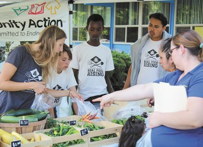 (L–R) Real Food Rising's Sara Simmons oversees teen employees Lilly Slack, Oliver Nsengiyumva and Oscar Arriaga at Urban Greens Market, which provides healthy food for the Glendale and Poplar Grove communities of SLC. Photo: John Barkiple