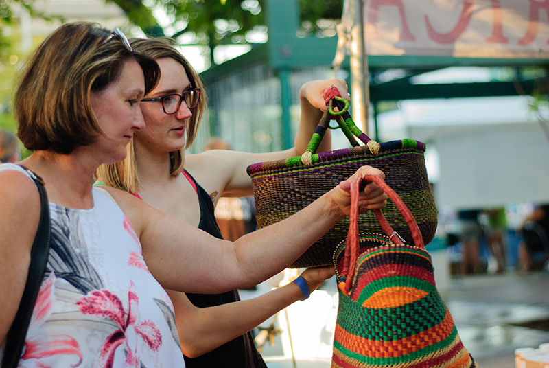 (L–R) Lisa and Savannah Manwill examine baskets at the Mama Africa craft booth. Photo: @snowlenda
