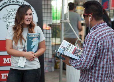 SLUG Mag teamster Sam Smith talks shop with a DIY Fest attendee. Photo: @snowlenda