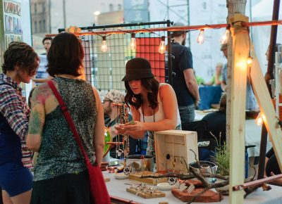 Rachel Ouzounian shows a piece of jewelry to customers at her Copper Elephant booth. Photo: @snowlenda
