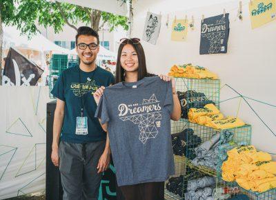 (L–R) Craft Lake City Merch Coordinator Francisco Ortega and SLUG Editorial Assistant Kathy Zhou look at shirts in the Craft Lake City merch booth. Photo: @clancycoop