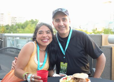 (L–R) Noemi Hernandez and Art Fermanian escape the Gallivan Plaza's sunshine on the shady CLC VIP Patio. Hernandez is on the Zoo, Arts & Parks (ZAP) board and works for Granite School District as the fine arts specialist. Photo: John Barkiple