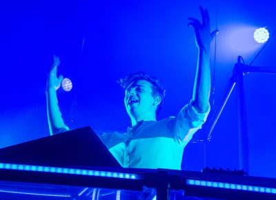 As the light stage fades to a tranquil blue, Flume raises his arms to captivate the frenzied crowd. Photo: Colton Marsala