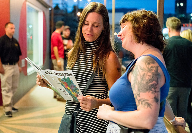 Andrea Washburn and Amy Batchler hang outside of The State Room and read the awesome September Local Food issue of SLUG Magazine. Photo: JoSavagePhotography.com