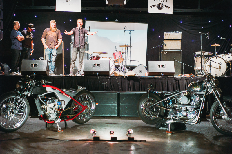 "Jason ""Rev"" Clark announces the winners of the bike building contest: Don Cash for individual builds, and Adam Paul and Ryan Friedli for the invited builds class. Photo: @clancycoop"