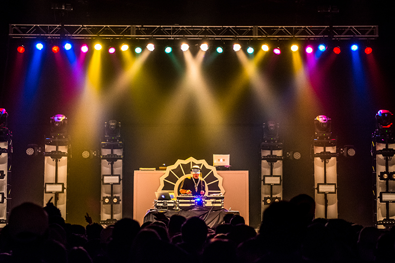DJ Whooligan mixes underneath a variety of colored spotlights.