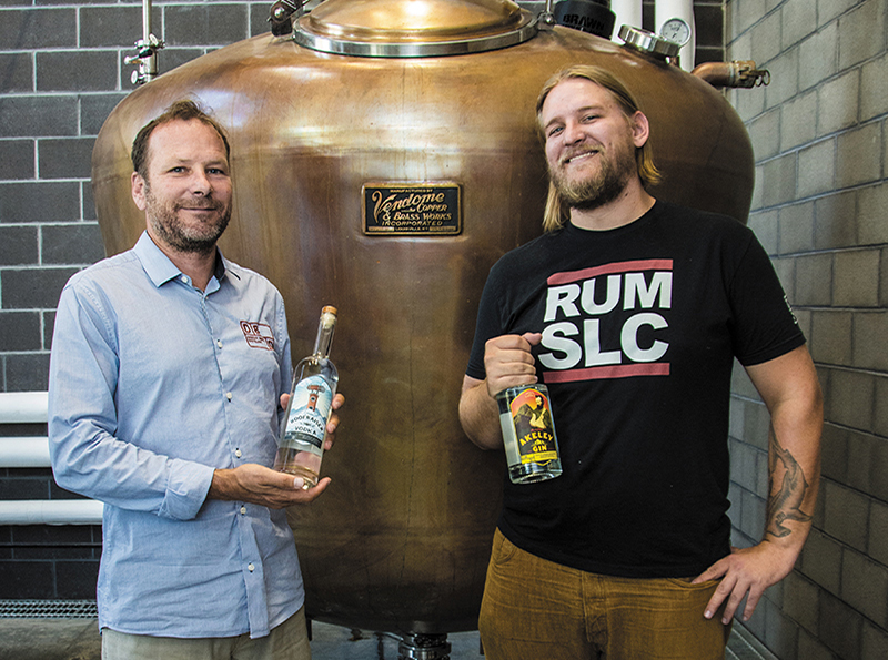 (L–R) Dented Brick Founder Marc Christensen and Head Distiller Ethan Miller celebrate the hard-earned, recent release of their Roofraiser Vodka and Akeley Gin.