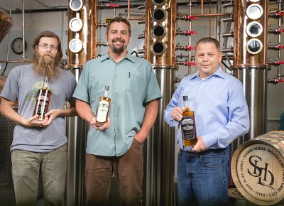 (L–R) Assistant Distiller Richard Malyn, Head Distiller Eric Robinson and Owner James Fowler create genuine craft spirits from start to finish at Sugar House Distillery.