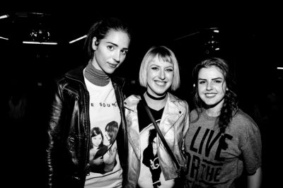 (L–R) Sandra, Jenica, and Katelyn wait near the merch booth for The Sounds to come on. Photo: Gilbert Cisneros