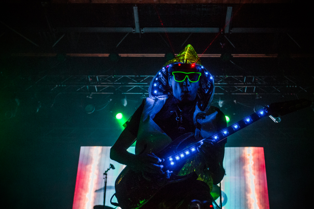 Through the darkness comes a blue-lit, laser-pointing, neon-glasses-wearing Steve Vai. Photo: Talyn Sherer