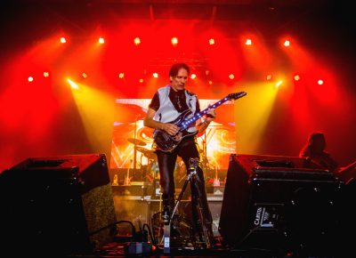 Within the blink of an eye, the lights come up, and the entire mood changes as Steve Vai continues to shred the guitar. Photo: Talyn Sherer