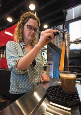Jack Mormon Coffee Manager Sydney Groesbeck pours a cup of the coffee roaster's nitro cold brew.