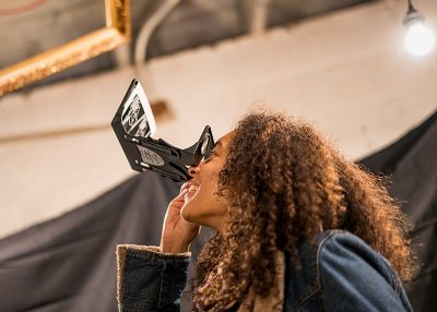 Darby Mest looking through stereo viewers in Tom Shrieve's exhibit. Photo: Jo Savage // @SavageDangerWolf