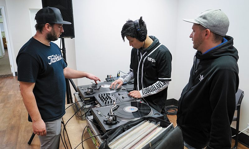 L–R) DJ SkratchMo, student Han Ying Yang and DJ Chaseone2 engage in DJ lessons that the Bboy Federation organizes. Photo: Jayson Ross