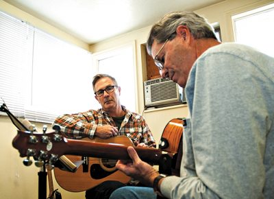(L-R) Guitar instructor Kim Driggs mentors student Larry Hjalmarson at Acoustic Music Studios. Photo: Scott Frederick