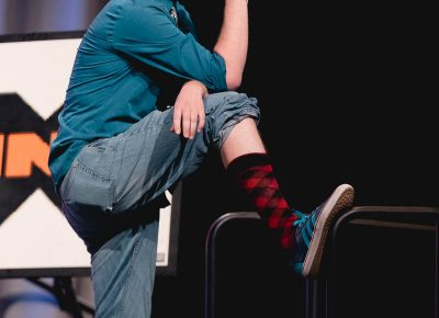 Host Chris Provost gives the audience a gratuitous view of his snazzy new socks. Photo: Lmsorenson.net