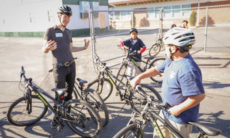 Bike Utah Youth Education Coordinator Jace Burbidge teaches the ins and outs of bicycle safety to Edison Elementary students. Photo by John Barkiple