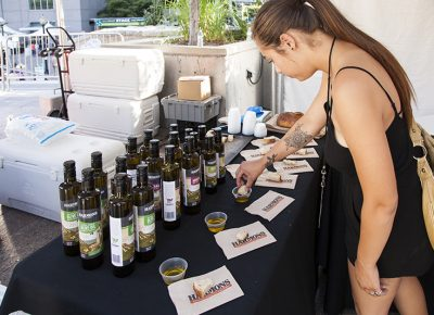 A young woman samples Harmons own brand of olive oil. Photo: @jbunds