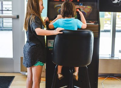 A vintage arcade cabinet is remastered with the art and design of a newage 8-bit game. Photo: @taylnshererphoto