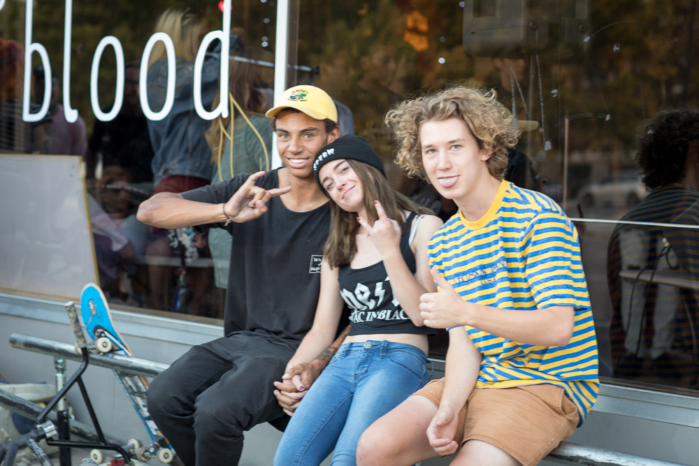 (L–R) Adrian Evans, Madeline Schierbaum and Jake Knaphus hold to the iron rail in front of Gold Blood's new storefront. Knaphus described Evans, who sometimes rides for 5050, as the instigator behind many of Salt Lake's community-related BMX events. Photo: John Barkiple