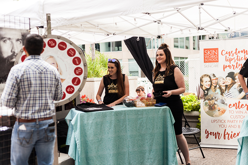The lovely ladies of Skinworks invite guests to play spin the wheel and win some free stuff. Photo: Chris Gariety