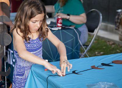 A little girl presses down a paper star on her craft. Photo: @jbunds