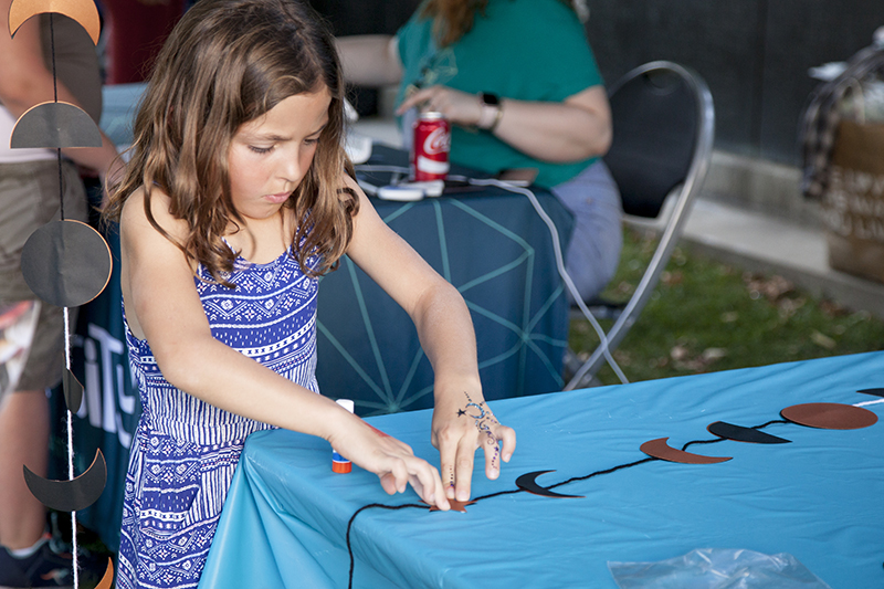 A little girl presses down a paper star on her craft. Photo: @jbunds