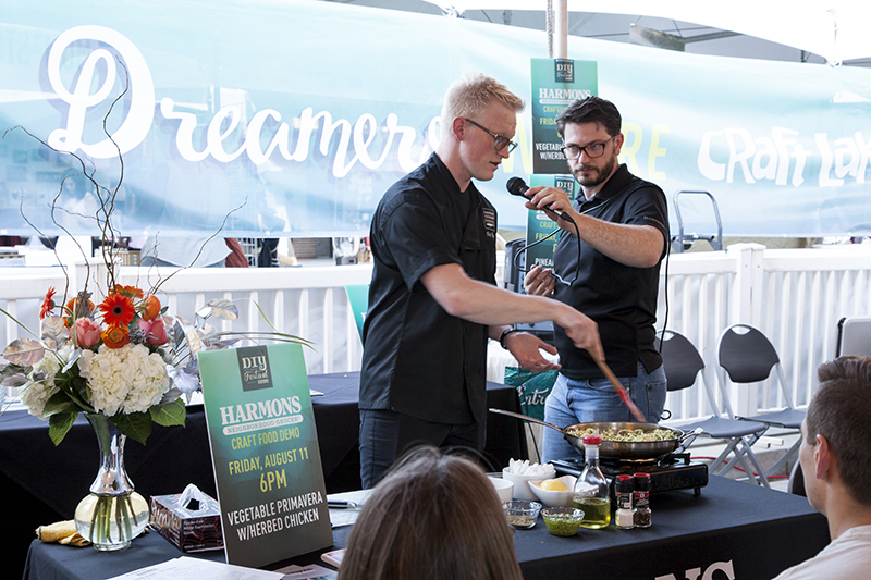 A Harmons Cooking School instructor shows the VIP audience how to make vegetable primavera with herbed chicken at their craft food demo. Photo: @jbunds