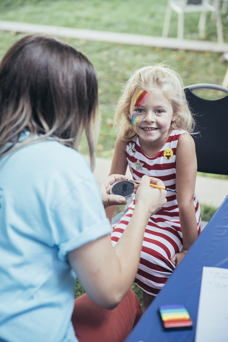 An excited girl halfway through her Pink Floyd Dark Side of the Moon face painting. Photo: @william.h.cannon