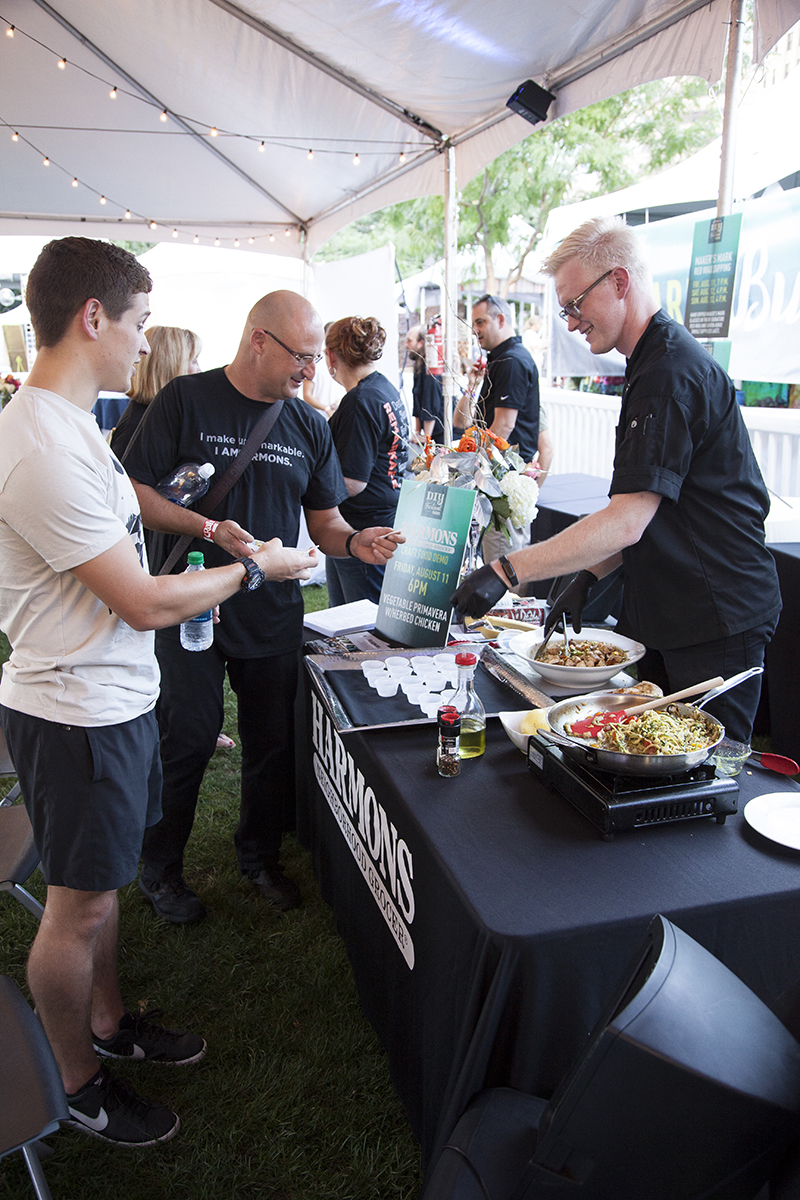 A Harmons Cooking School instructor divvies out samples of vegetable primavera with herbed chicken, made during a craft food demo, to the patrons in the VIP area. Photo: @jbunds