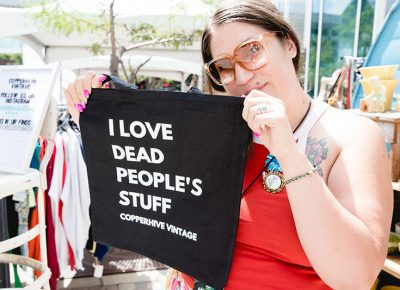 """Jaqueline Whitmore showing off the popular """"I love dead people's stuff"""" tote bag at her shop, Copperhive Vintage. LmSorenson.net"""