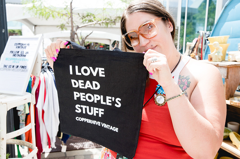 "Jaqueline Whitmore showing off the popular ""I love dead people's stuff"" tote bag at her shop, Copperhive Vintage. LmSorenson.net"