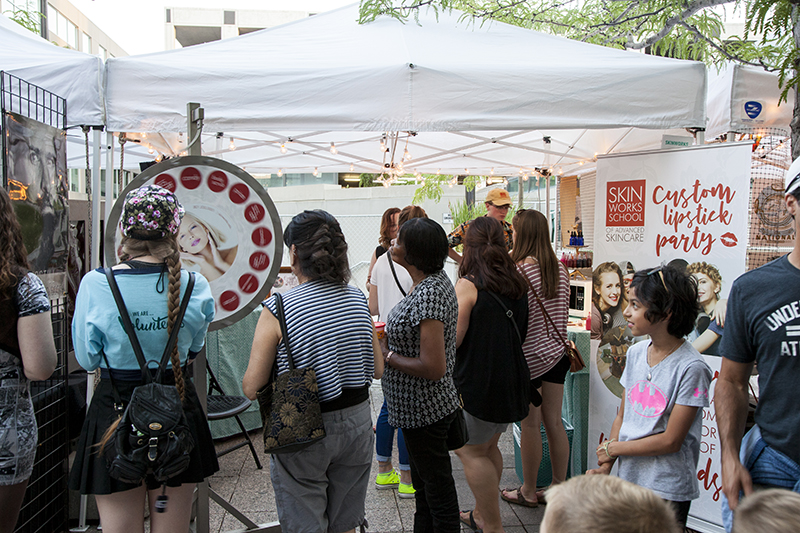 Women at the Skinworks booth watch the wheel spin around, hoping to win free prizes. Photo: @jbunds
