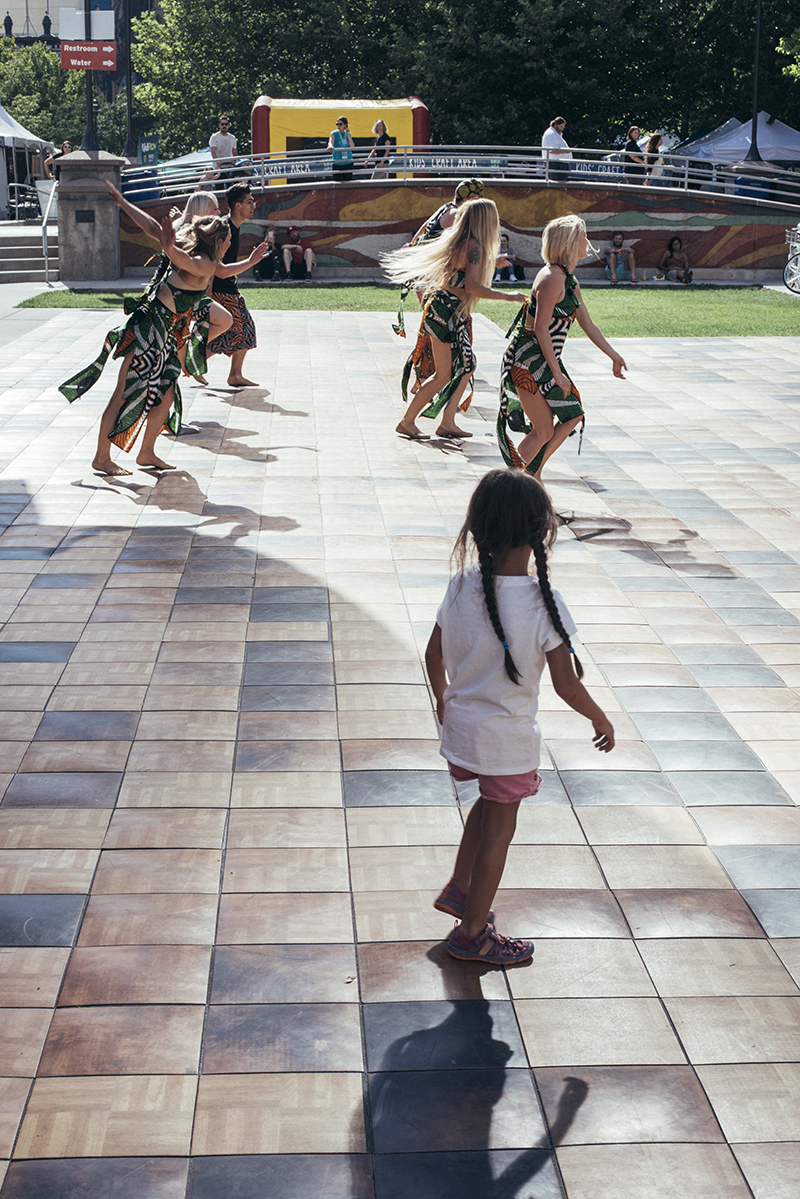 A girl enthralled by the dancers accompanying a drumming group. Photo: @william.h.cannon