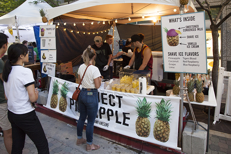 A woman orders at the front of a line for drinks from Perfect Pineapple. Photo: @jbunds