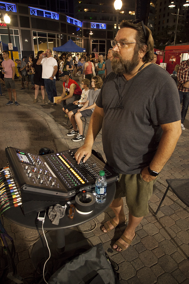 90.9FM KRCL Stage sound engineer John adjusts the levels for a performing band. Photo: @jbunds