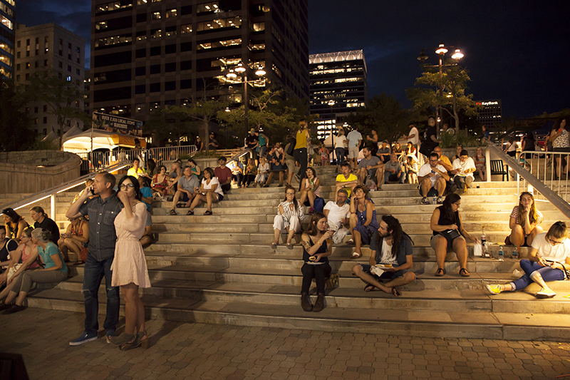 Patrons sit on the steps of the Gallivan Center watching a band at the south end of the festival. Photo: @jbunds