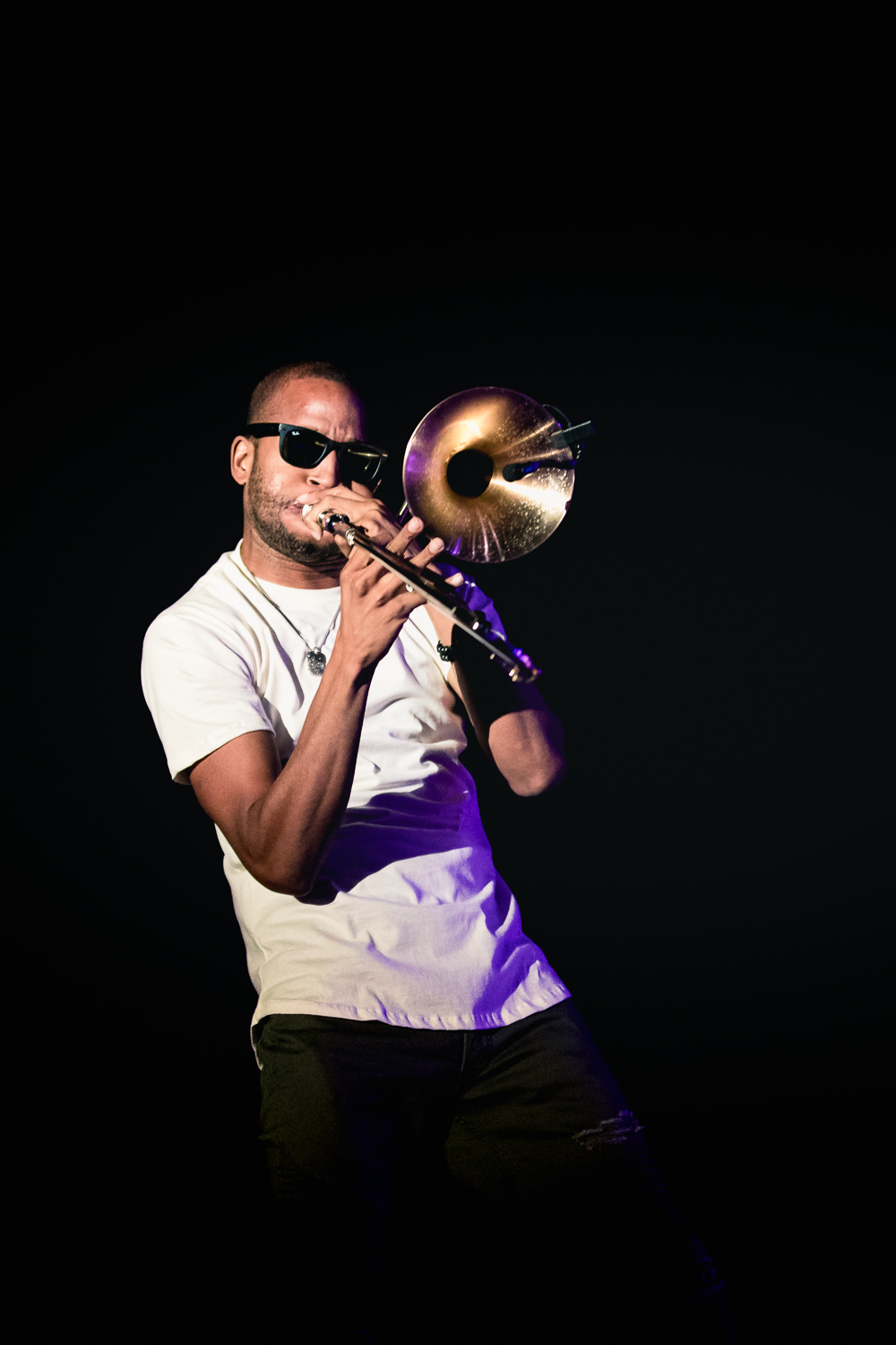 Trombone Shorty stepping out of the main stage lights and closer to the audience in the shadows. Photo: Lmsorenson.net