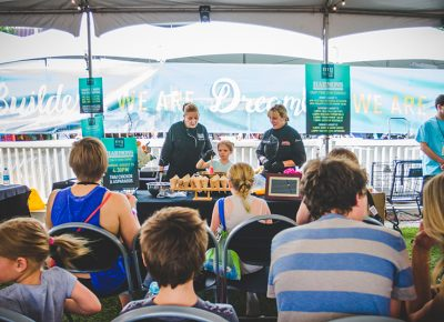 A young festival-goer assists the Harmons chefs with their Thai chicken–and-asparagus cooking demo. Photo: @taylnshererphoto